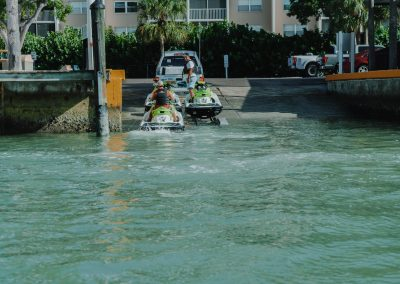 Three jet skis being loaded into the ocean off of Marco Island