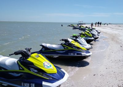 Row of parked jet skis on Marco Island beach